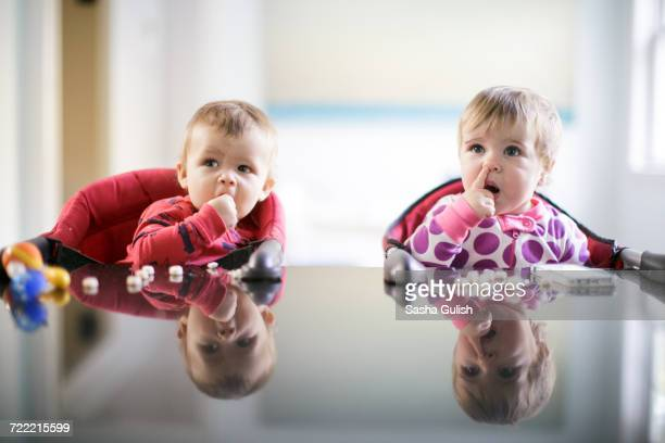 Male and female toddlers at kitchen counter picking nose and eating sweets
