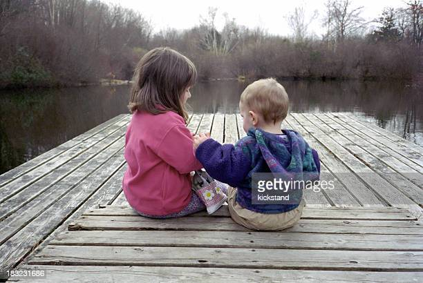 Male and female toddlers on a wooden dock facing a lake