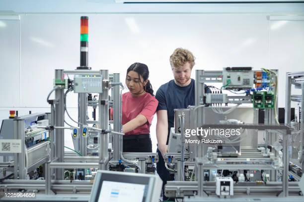 male and female trainee engineers inspecting robotic assembly line in unspecified. - monty rakusen stock pictures, royalty-free photos & images