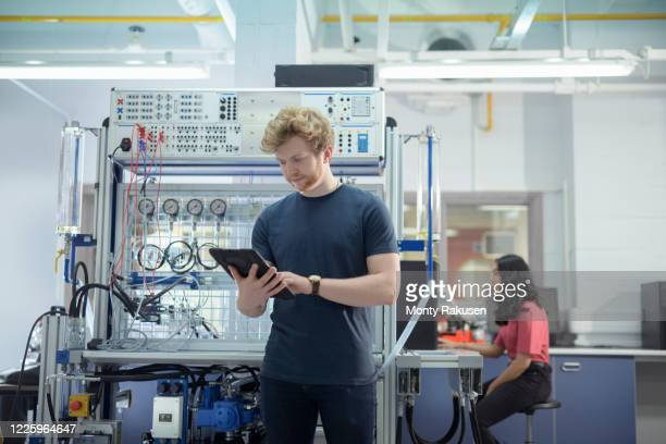 male and female trainee engineers with experimental equipment in unspecified. - monty rakusen stock pictures, royalty-free photos & images