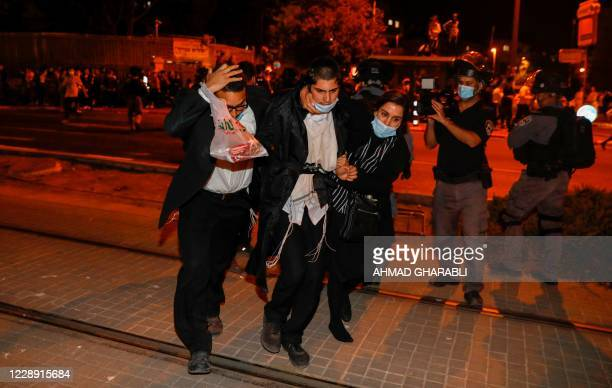 Male and female undercover Israeli security forces arrest an UltraOrthodox Jewish man during a protest against the enforcement of coronavirus...