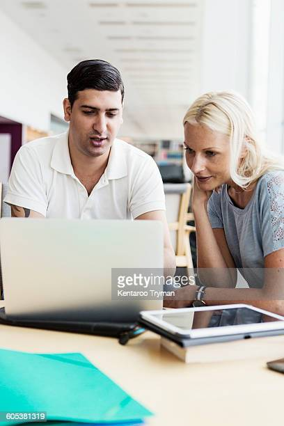 Male and female university students using laptop together at library