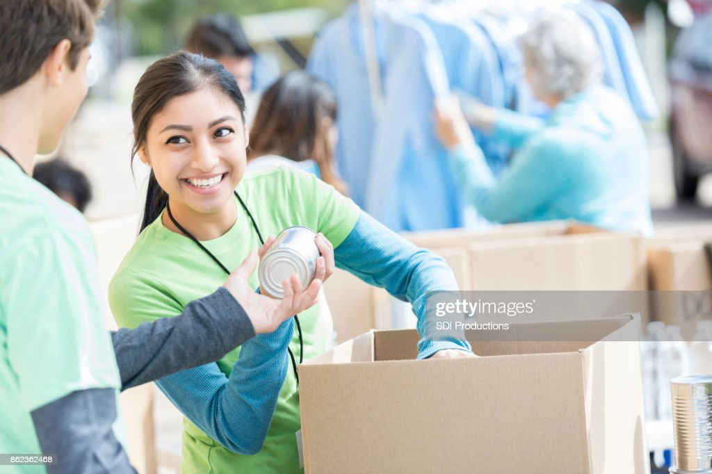 Male and female volunteers sort donations during food drive : Stock Photo