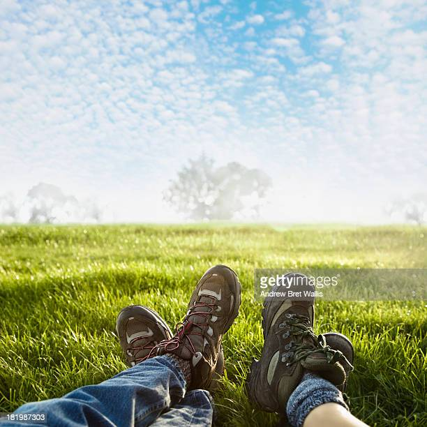 male and female walker relax in a sunlit meadow - meadow walker stock pictures, royalty-free photos & images