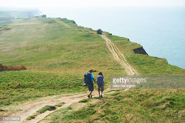 Male and female walking along path on cliff top