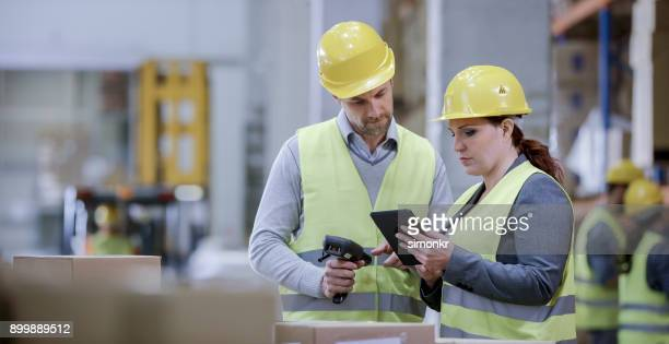 male and female warehouse supervisors talking about inventory check in warehouse - jacket stock pictures, royalty-free photos & images