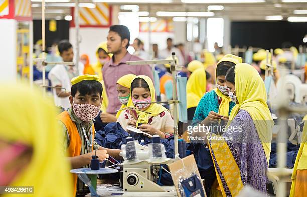 A male and female worker at sewing machines in the production facility of GBL Group textile manufacurer on October 07 2015 in Gazipur Bangladesh