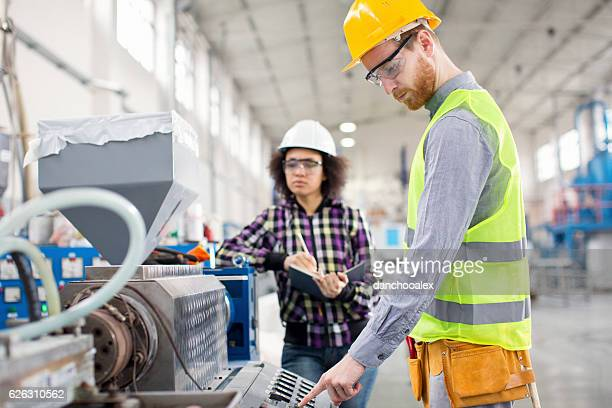 Male and female worker in factory working