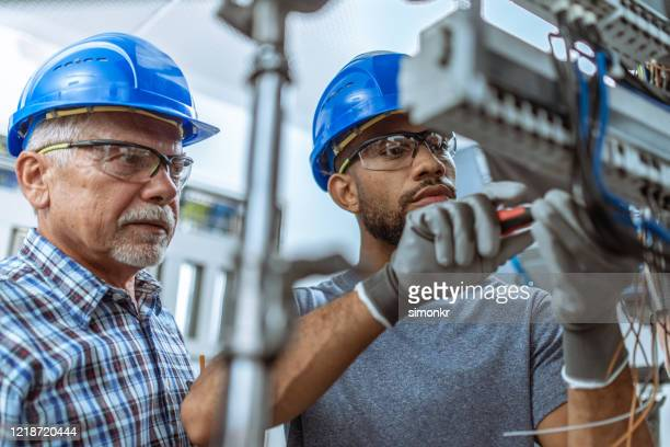 male apprentice connecting wires in the distribution board - power occupation stock pictures, royalty-free photos & images