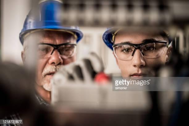 mannelijke leerling die draden in de distributieraad verbindt - stage stockfoto's en -beelden