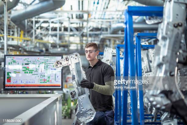 male apprentice engineer inspecting parts in car factory - expertise stock pictures, royalty-free photos & images