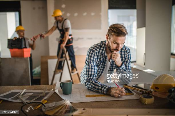 male architect drawing improvements on housing plan at construction site. - reform stock pictures, royalty-free photos & images