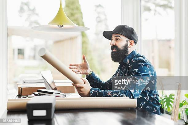 Male architect gesturing while working at home office