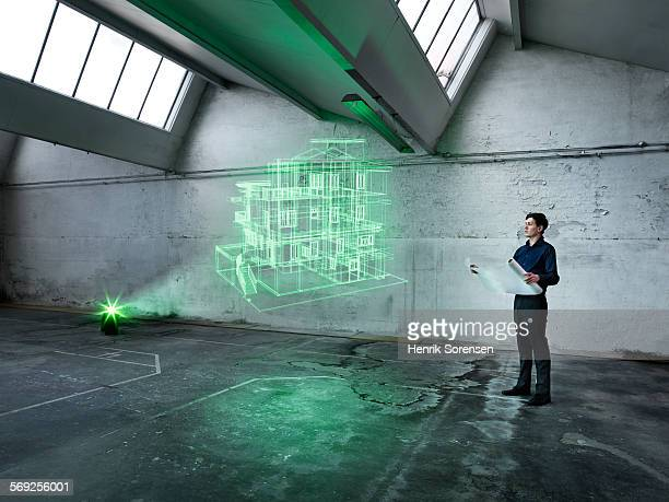 Male architect looking at a holographic house