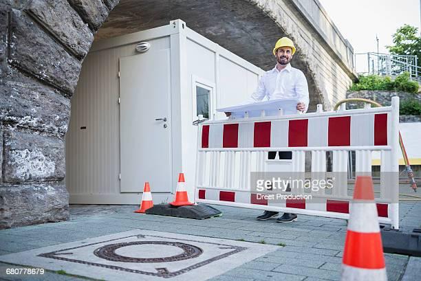 Male architect reading blueprint at construction site, Munich, Bavaria, Germany