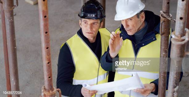 male architect showing investor how plan detail will be implemented into building - jacket stock pictures, royalty-free photos & images