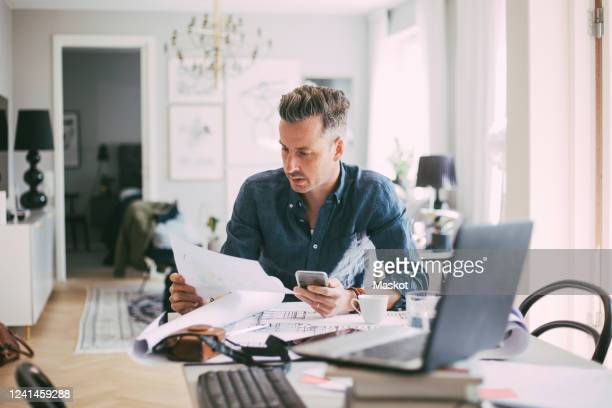 male architect sitting at workplace reading blueprint at home - document stock pictures, royalty-free photos & images