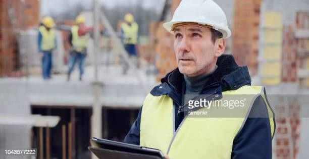 male architect standing at construction site and checking plans on digital tablet - protective workwear stock pictures, royalty-free photos & images