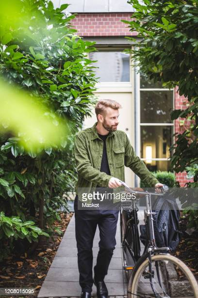 male architect with bicycle walking against house - 40 44 jahre stock-fotos und bilder