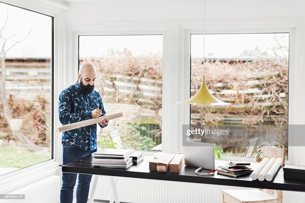architect home office. Male Architect Working At Table In Home Office By Window : Stock Photo