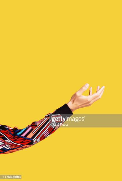 male arm and hand on yellow background - long sleeved stock pictures, royalty-free photos & images