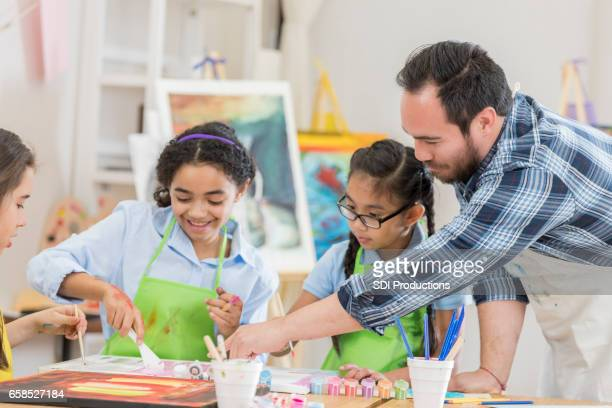 Male art teacher with works with students