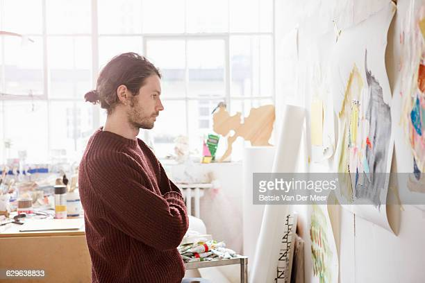 Male artist looks thoughful at painting on wall.