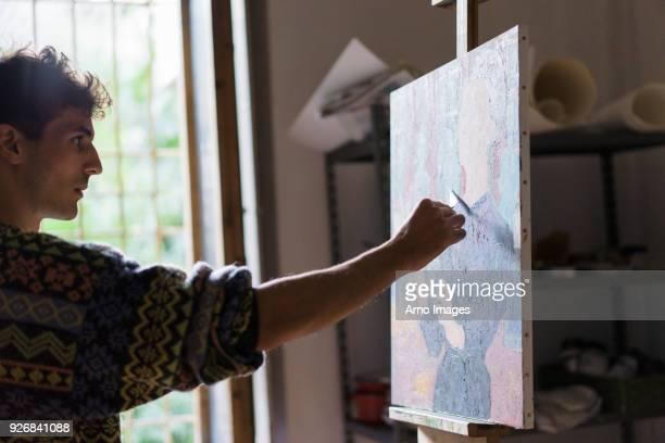 male artist painting canvas on easel in artists studio - staffelei stock-fotos und bilder