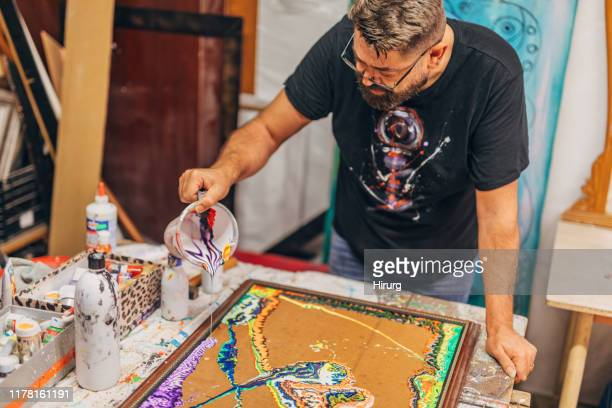 male artist painting in his art studio - acrylic painting stock pictures, royalty-free photos & images