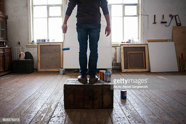 Male artist sitting on crate, looking at blank canvas, low section