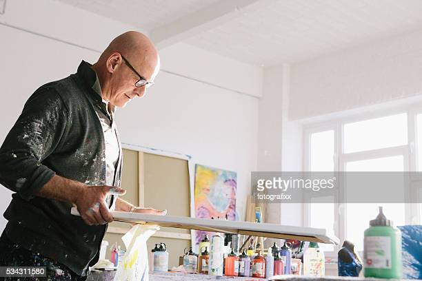 Männliche Künstler arbeiten auf seinem Gemälde in seinem studio