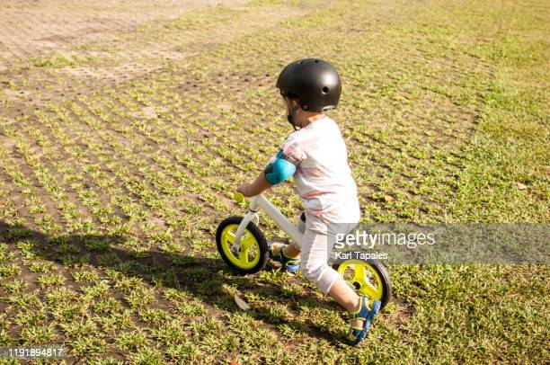 a male asian toddler is cycling outdoor - capital region stock pictures, royalty-free photos & images