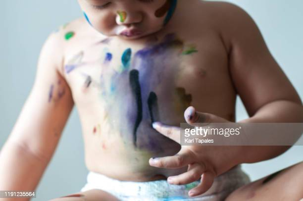 a male asian toddler is painting with watercolor - real body fotografías e imágenes de stock