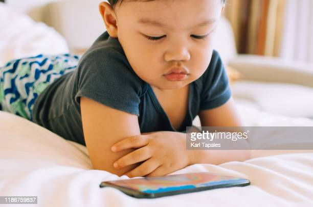 a male asian toddler is watching videos from a smartphone - surfer sur le net photos et images de collection