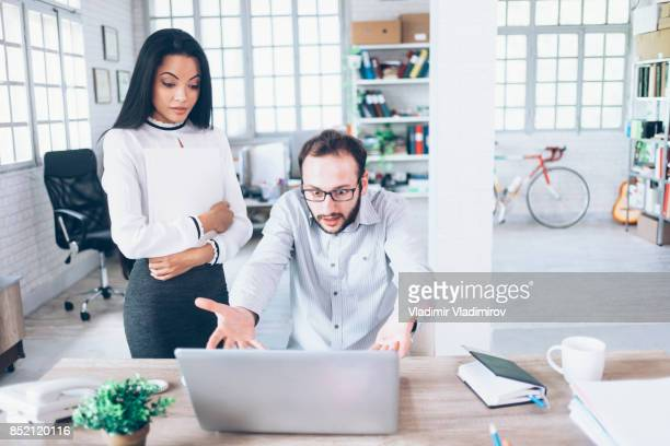 male assistant having laptop problems at work - computer bug stock photos and pictures