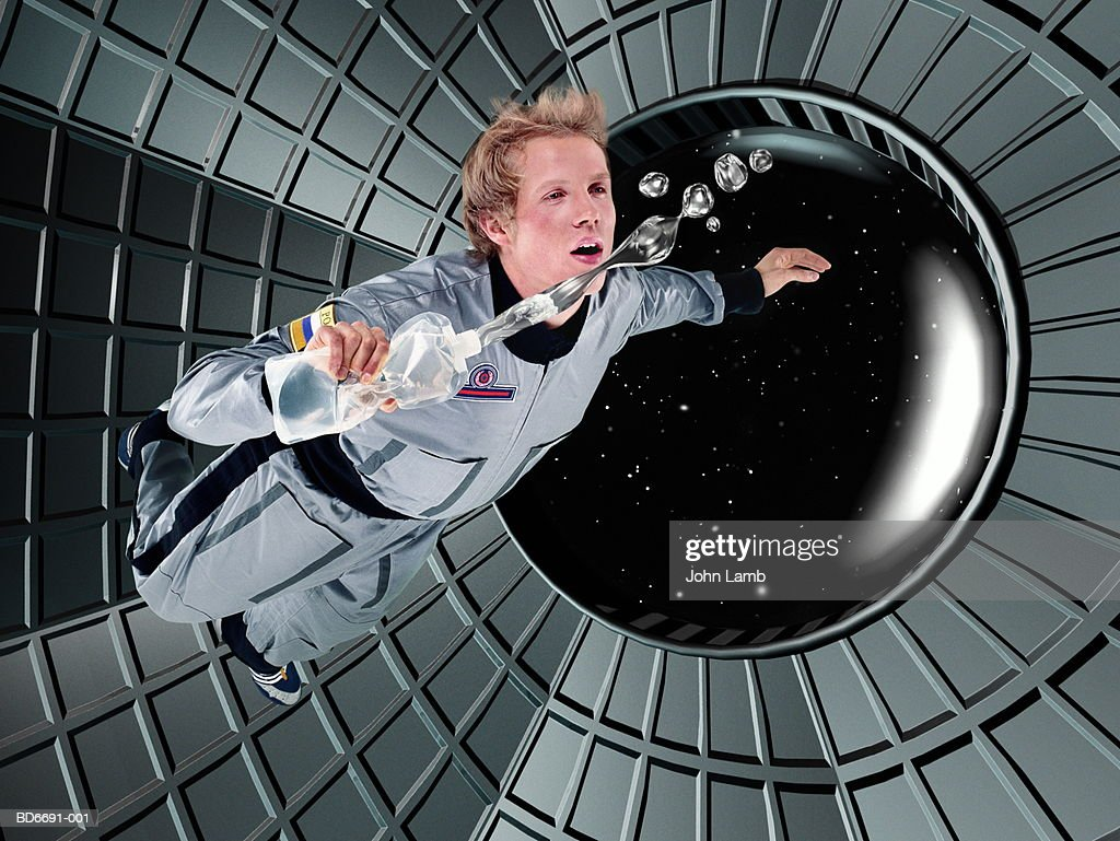 Male astronaut floating in space station (Digital Composite) : Stock Photo