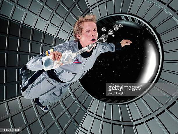 male astronaut floating in space station (digital composite) - space station stock pictures, royalty-free photos & images