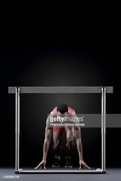 Male athlete at starting position in front of hurdle