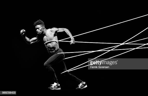 Male athlete being hold back by ropes
