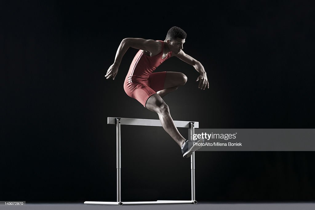 Male athlete cearling hurdle : Stock Photo