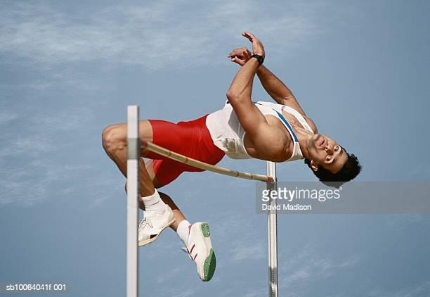 Male athlete clearing high jump bar