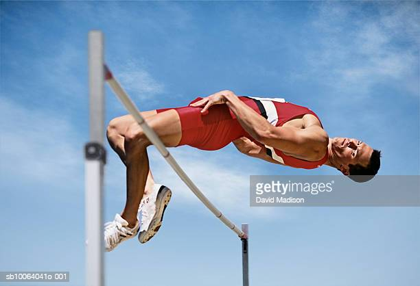 Male athlete clearing high jump bar