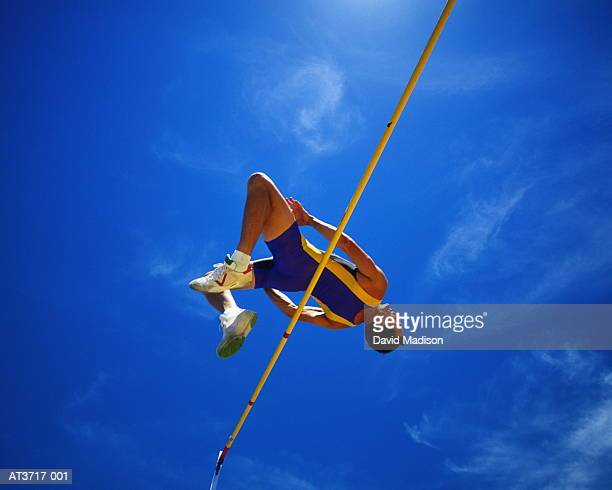 male athlete clearing high-jump bar, low angle view (enhancement) - high jump stock pictures, royalty-free photos & images