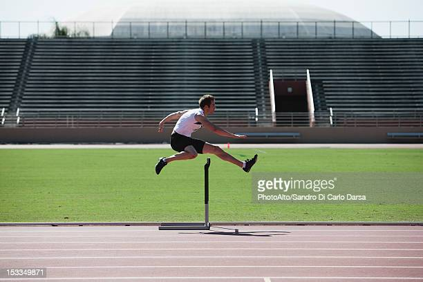 Male athlete clearing hurdle, side view
