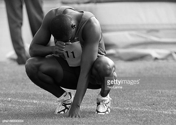 Male athlete crouching, concentrating, b&w