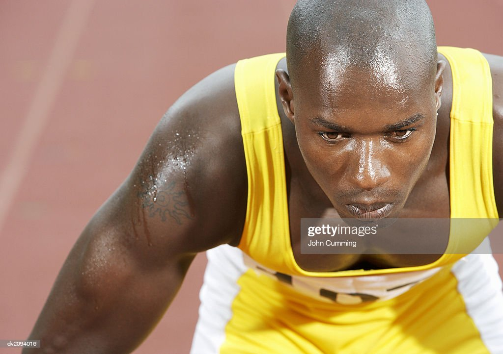 Male Athlete Crouching on Starting Blocks on a Running Track : Stock Photo