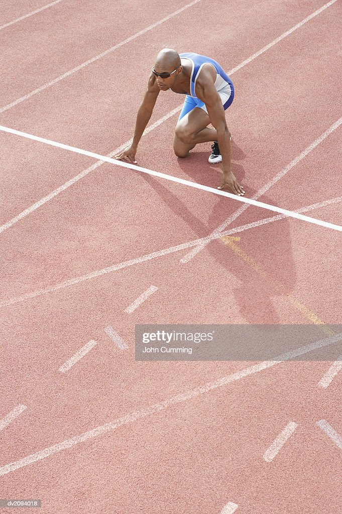 Male Athlete Crouching on the Starting Blocks of a Running Track : Stock Photo