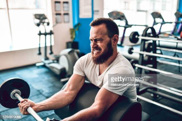 male athlete doing arm workout with barbell in gym - curling sport stock pictures, royalty-free photos & images
