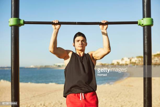 male athlete doing chinups on bar at beach - chin ups stock photos and pictures