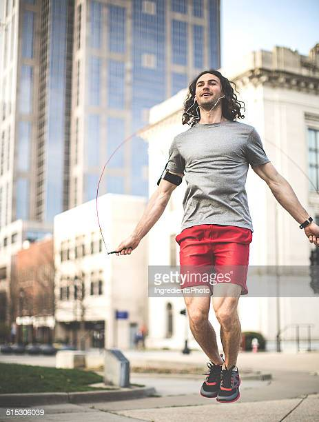 Male athlete doing his jumping rope workout in the city.